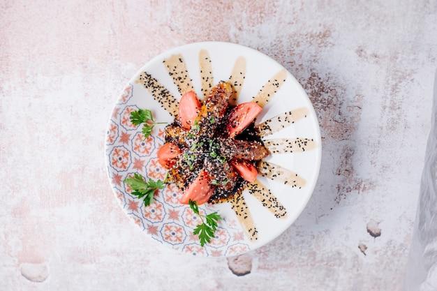 Carne grelhada com especiarias e fatias de tomate em molho teriyaki.