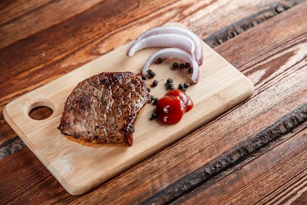 Carne grelhada com especiarias e molho de tomate em um fundo de madeira desgastado