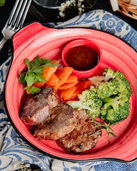 Carne grelhada com legumes vista lateral