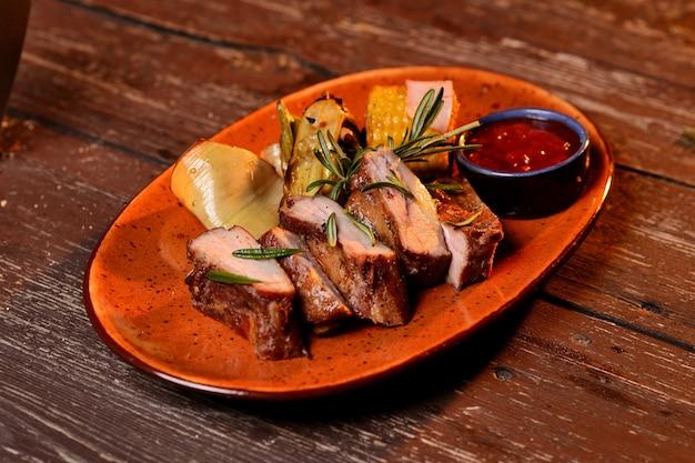 Carne grelhada com milho, molho e um raminho de alecrim. em uma mesa de madeira