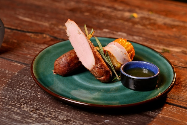 Carne grelhada com milho, molho e um raminho de alecrim. em uma placa verde em uma mesa de madeira