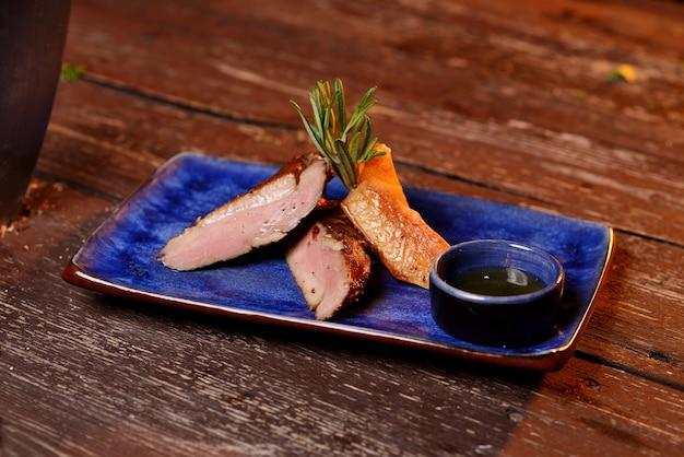 Carne grelhada com molho e alecrim. em uma placa azul em uma mesa de madeira