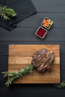 Carne grelhada com verduras e molho em uma tábua de cortar em um fundo preto de madeira