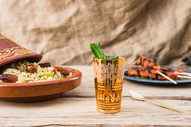 Carne grelhada e salada de quinoa com ameixas secas perto de copo na mesa