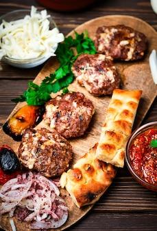 Carne grelhada. foco seletivo do close-up. bolinhos de carne ou costeletas - kofte turco feito de cordeiro e boi com queijo e especiarias. em uma travessa de madeira com legumes grelhados, ervas e molho.