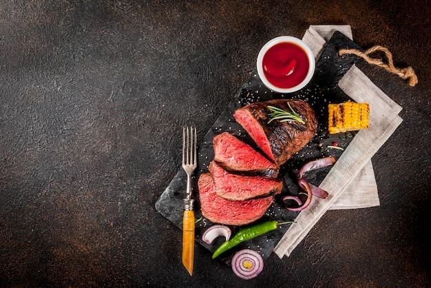 Carne grelhada fresca, carne caseira de churrasco médio rara, na tábua de pedra preta, com especiarias, fundo escuro, copie o espaço acima