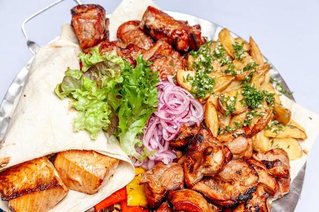 Carne grelhada mista, vegetais fritos e filetes de salmão grelhado em prato quente