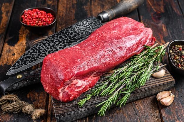 Carne inteira crua de filé mignon para filé mignon em uma tábua de madeira com faca de açougueiro. fundo de madeira escuro. vista do topo.