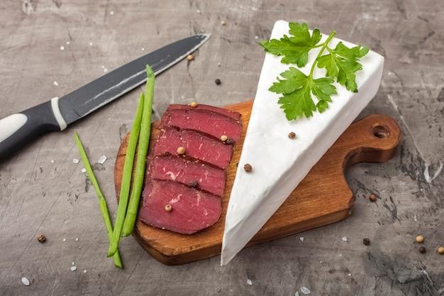Carne jerky em uma tábua de madeira, corte e cebolinha. queijo de pasta mole com mofo branco