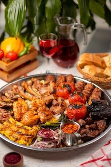 Carne, kebab de frango, churrasco com batatas assadas e grelhadas, tomate e arroz.