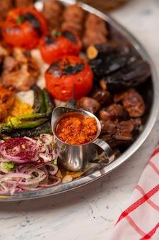Carne, kebab de frango, churrasco com batatas assadas e grelhadas, tomate e berinjela.