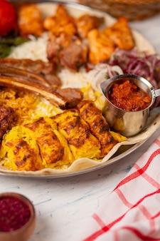 Carne, kebab de frango, churrasco com batatas assadas e grelhadas, tomate e servido com arroz.