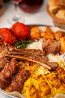 Carne, kebab de frango, churrasco com batatas assadas, grelhadas, tomates e servido com arroz.