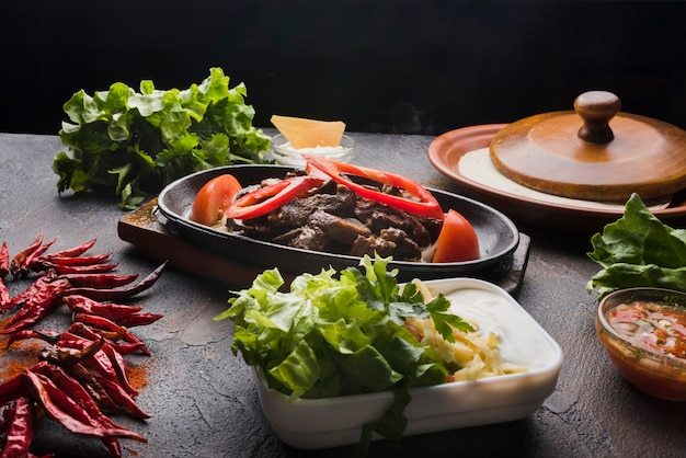 Carne, legumes e aperitivo na mesa de madeira