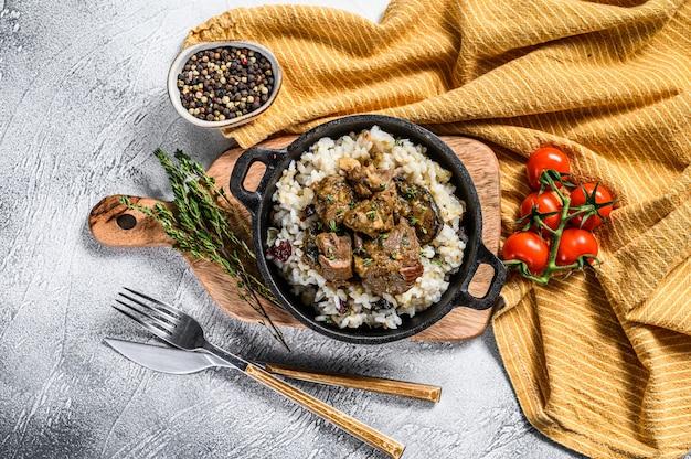 Carne madras com arroz basmati em uma panela com uma toalha de mesa