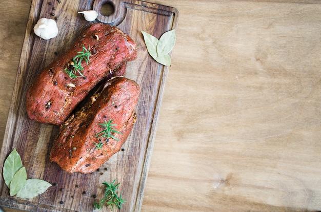 Carne marinada crua fresca em uma tabela de madeira.