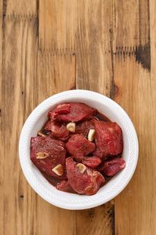 Carne marinada em chapa branca na superfície de madeira
