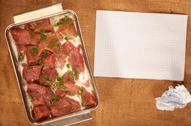 Carne marinada no leite e verduras em um prato fundo de aço em um pano caseiro com folhas limpas de papel e uma caneta esferográfica