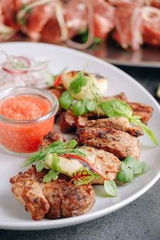 Carne marinada para churrasco grelhada e servida em prato branco.