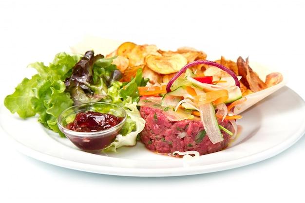 Carne moída crua com batatas fritas e salada