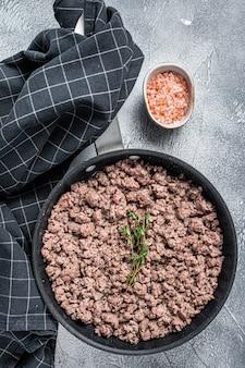 Carne moída de carne bovina e suína frita em uma panela com ervas