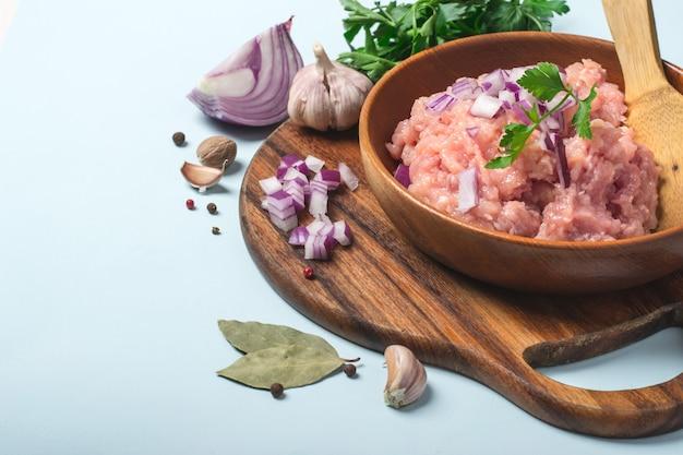 Carne moída de frango cru em uma tigela com especiarias