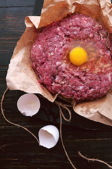 Carne moída em um saco de papel com um ovo cru