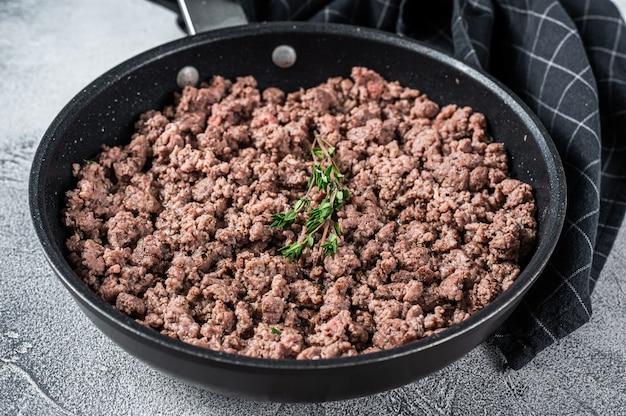 Carne moída frita e carne de cordeiro em uma panela com ervas