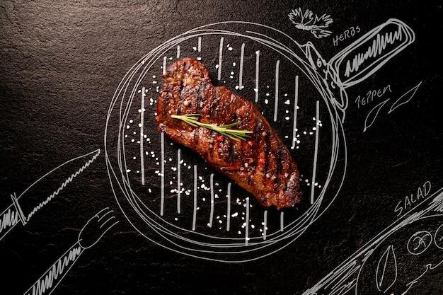 Carne na lousa preta com panela pintada e ingredientes. vista do topo. conceito de churrasco.