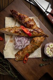 Carne no pão sírio com alho em uma mesa de madeira