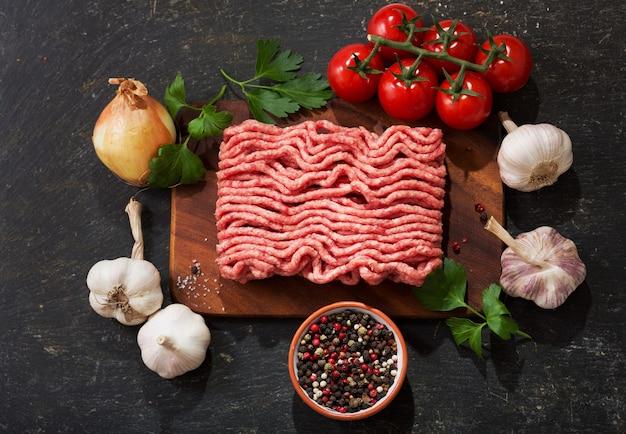 Carne picada com ingredientes para cozinhar em tábua de madeira, vista superior
