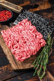 Carne picada crua, carne moída com ervas e especiarias em uma tábua de madeira. fundo de madeira escuro. vista do topo.
