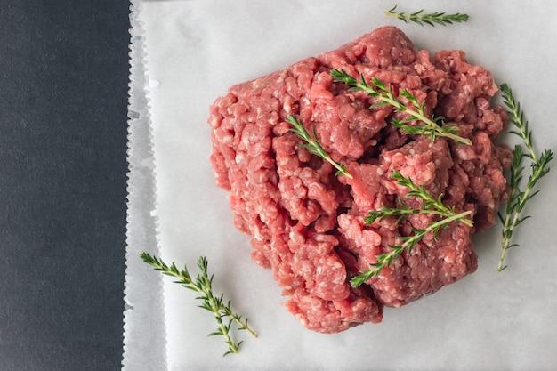 Carne picada crua com tomilho e especiarias para cozinhar costeletas.