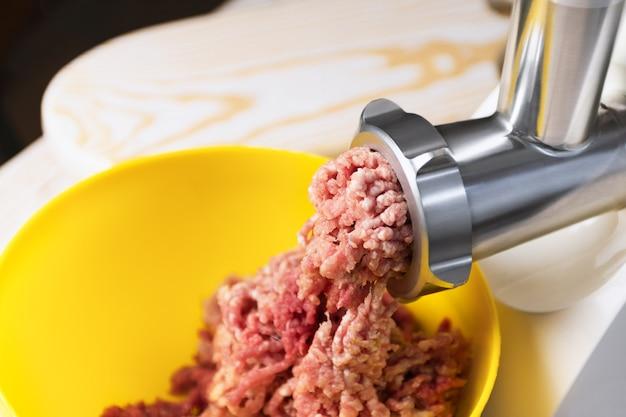 Carne picada em um moedor de carne elétrico