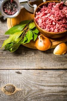 Carne picada em uma tigela, moedor e temperos com ervas