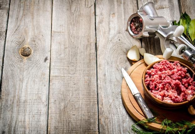 Carne picada preparada em uma tigela, moedor e especiarias com ervas. em uma mesa de madeira. espaço livre para texto.