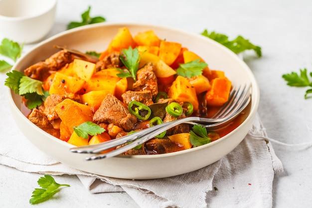 Carne picante cozida com as batatas no molho de tomate na placa branca. goulash tradicional de carne.