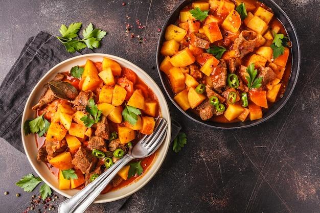 Carne picante cozido com as batatas no molho de tomate, vista superior. goulash tradicional de carne.