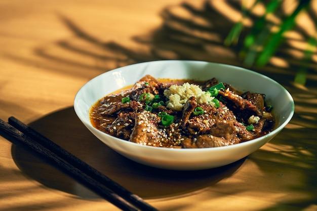 Carne picante sichuan em um molho picante, alho, pimenta, sementes de gergelim em uma tigela branca. cozinha chinesa. shuizhu, shui zhu