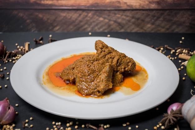 Carne rendang comida tradicional tradicional em prato branco e fundo preto