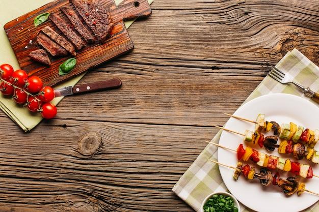 Carne saborosa fresca e bife na superfície de madeira