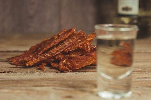 Carne seca deliciosa em um fundo de madeira. produtos em embalagens artesanais. lanche para álcool. foto macro. fechar-se.