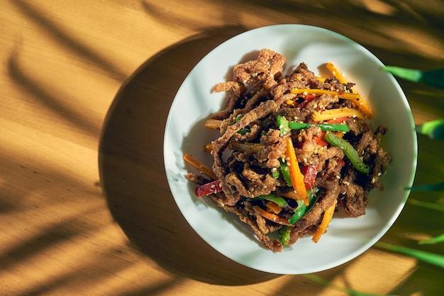 Carne seca picante sichuan wok com pimenta, sementes de gergelim, cenoura e tomate verde em uma tigela branca. cozinha chinesa