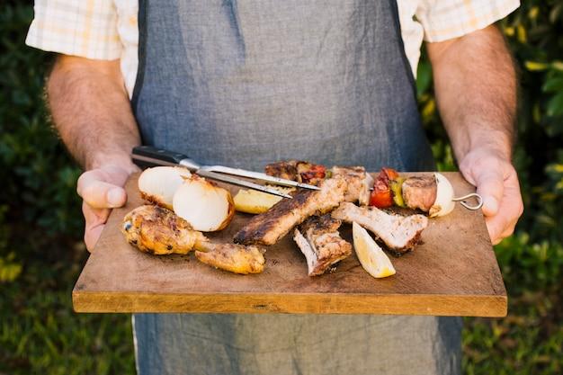 Carne suculenta grelhada e legumes na mesa de madeira nas mãos