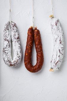 Carne tradicional de linguiça curada pendurada na superfície branca.