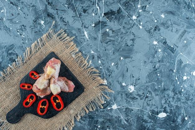 Carnes de frango cruas e pimenta fatiada em uma tábua de corte na serapilheira na superfície azul