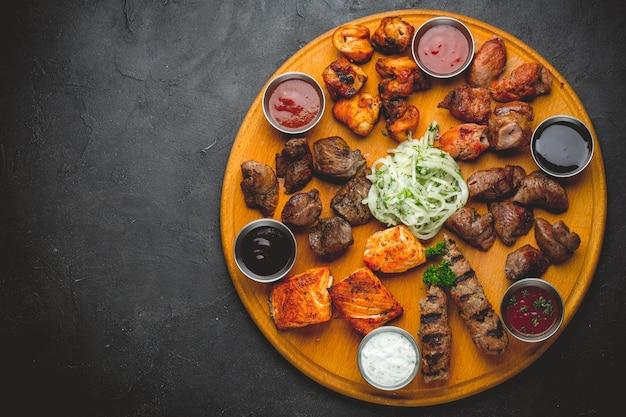 Carnes e molhos grelhados assorted em uma tabela de madeira.
