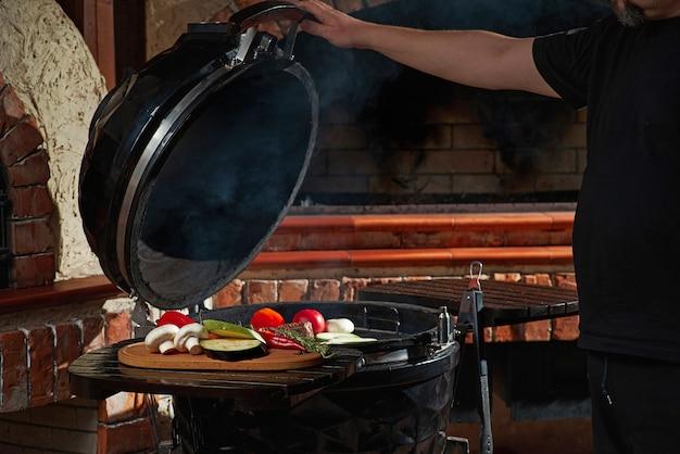 Carnes frescas e vegetais grelhados em um churrasco caseiro de fim de semana. conceito de cozinha, cozinha escura.