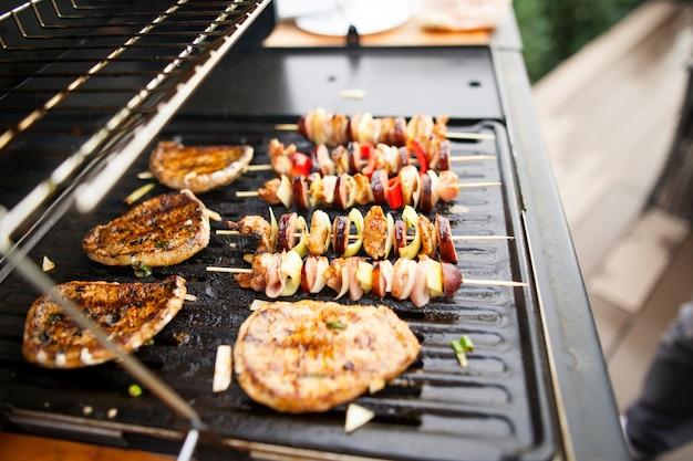 Carnes frescas e vegetais grelhados na grelha a gás, prontos para comer