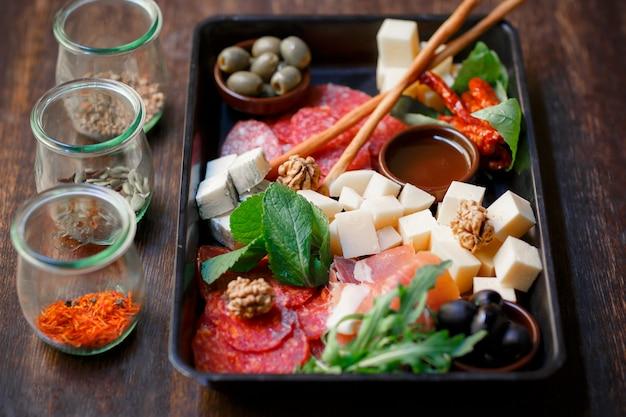 Carnes frias de prato de antipasto com palitos de pão, presunto, fatias de presunto, charque, prato de salame e queijo na placa de madeira sobre a mesa rústica.